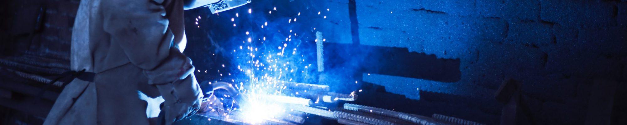 man-wearing-welding-helmet-welding-metal-near-gray-brick-1474993